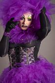 stock photo of transexual  - Drag queen in violet dress standing on gray background - JPG