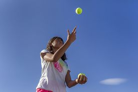 stock photo of juggling  - A girl tries juggling against a bright blue sky - JPG