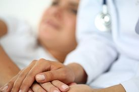 stock photo of compassion  - Friendly female doctor hands holding patient hand lying in bed for encouragement empathy cheering and support while medical examination - JPG