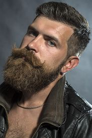 image of moustache  - Portrait of brutal sullen handsome unshaven man with lush beard and moustache in brown leather biker jacket in chain looking forward on grey background vertical picture - JPG