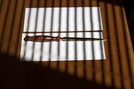 picture of jalousie  - One sharp golden paper knife with brown wooden handle lying on two white envelopes on office table on jalousie shadow background horizontal picture - JPG