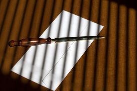 pic of jalousie  - Elegant sharp golden paper knife with brown wooden handle lying on one white envelope on office table on jalousie shadow background horizontal picture - JPG