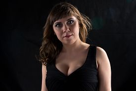 stock photo of curvy  - Photo of curvy woman with flowing hair on black background - JPG