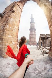 pic of qutub minar  - Woman in red costume leading man by hand to Qutub Minar tower in Delhi India - JPG