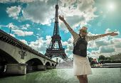 Woman tourist selfie near the Eiffel tower in Paris under sunlight and blue sky. Famous popular tour poster