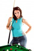 Sexy young woman in jeans and a hat with a pool cue and standing at  the table