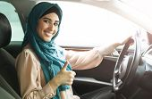 Happy Arabian Woman Wearing Hijab Driving Her Car With Thumbs Up Gesture. Get Driving License Concep poster