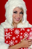 Sexy blond snow bunny in a white furry coat and hat holding a Christmas present over a red background poster