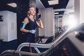 Happy Women Jogging On A Treadmill. Training On Cardio To Maintain Good Health. Comfortable Clothing poster