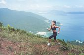 Slender Young Female Athlete Doing Cardio Exercise Going Up The Mountain With Sea In Background. poster