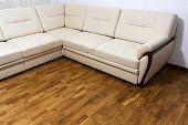 Big New Beige Sofa On Wooden Parquet Floor poster