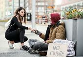 Young Woman Giving Money To Homeless Beggar Man Sitting In City. poster