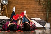 Romantic Couple Lying On Wooden Floor Near The Bed And Holding Red Hearts Shape At Home. True Feelin poster