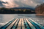 Mole (pier) On The Lake. Wooden Bridge In Forest In Winter Time With Blue Frozen Lake. Lake For Fish poster