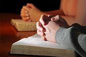 foto of praying hands  - A husband and wife praying together with their Holy Bibles  - JPG