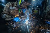 Man Welder In Welding Mask, Building Uniform And Blue Protective Gloves Welds Metal Car Muffler With poster