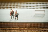 stock photo of miniature golf  - miniature train set figures on a station platform with golf clubs - JPG