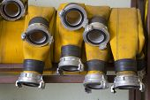 stock photo of firehose  - Zoomed yellow firehose are hanging on warehouse shelfs - JPG