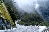 stock photo of icy road  - Steep icy mountain road in winter leading to Haast Pass in New Zealand - JPG