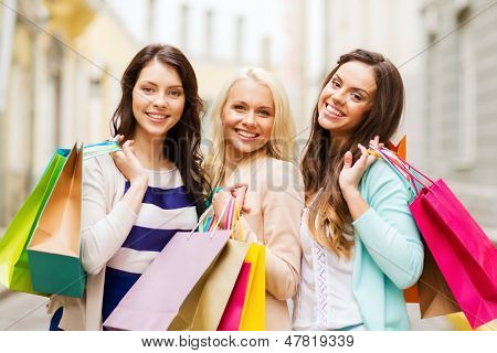 shopping and tourism concept - beautiful girls with shopping bags in ctiy poster