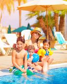 Big family relaxed near poolside, happy young mother with three sweet child have fun outdoors on tro