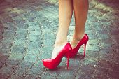 woman legs in red high heel shoes outdoor shot on  cobble street