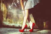 stock photo of shoe  - woman legs in red high heel shoes and short skirt outdoor shot against old metal door - JPG