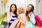 shopping and tourism concept - beautiful girls with shopping bags in ctiy t-shirt