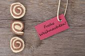 picture of weihnachten  - the german words Frohe Weihnachten which means merry christmas on a red label with cookies as background - JPG
