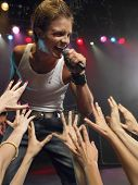 picture of adoration  - Young man singing on stage in concert close to adoring fans - JPG