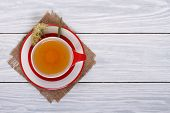 picture of lime-blossom  - Tea with lime in a red cup on a wooden table - JPG