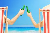 Man and woman relaxing on a beach and cheering with beer bottles, on a beach next to a sea