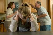 image of child abuse  - teenage girl covers her ears as her parents argue loudly behind her - JPG