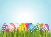 stock photo of easter-eggs  - Colourful easter eggs placed over green grass - JPG