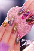 picture of nail-art  - Human fingers with long acrylic fingernail and beautiful manicure holding pink heart - JPG