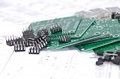 pic of transistor  - Circuit boards and electronic components with schematics in background - JPG