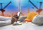 picture of tool  - hand of architect working on table with tablet computer and working tool equipment against reflection of office building and crane construction use for civil engineering and construction industry business - JPG