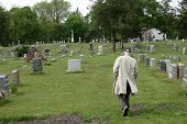 stock photo of life after death  - An elderly man pays his respects at a cemetery - JPG