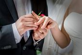 picture of marriage ceremony  - Groom placing a wedding ring on the finger of his bride during a wedding ceremony  - JPG