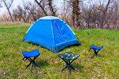 stock photo of wander  - Tourist tent with three chairs on green meadow - JPG