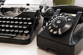 pic of outdated  - Vintage telephone and typewriter standing on the desk in the office