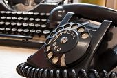 picture of outdated  - Vintage telephone and typewriter standing on the desk in the office