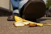 image of slip hazard  - person about to slip on a banana peel or banana skin  - JPG