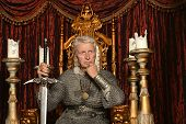 foto of throne  - Mature pensive medieval knight on the throne - JPG