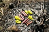 foto of ember  - Raw sausages and peppers preparing on hot fireplace wood embers during picnic in forest meadow - JPG