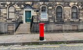 stock photo of postbox  - Typical red british postbox in front of the houses - JPG