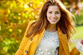 foto of october  - Beautiful elegant woman standing in a park in autumn  - JPG