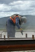 stock photo of sandblasting  - tradesman sandblasting steel beams for building project - JPG