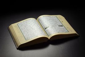 foto of islamic religious holy book  - Islamic Book Holy Quran Under Soft Light on Black Background - JPG