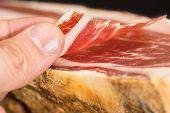 foto of shoulder-blade  - Caucasian man left hand taking serrano ham slice - JPG